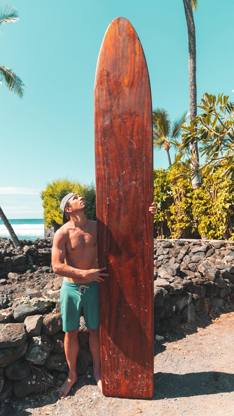 Havaí: Hugo Pinheiro ao lado de uma velha prancha de surfe de madeira Foto: Red Bull